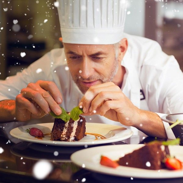 Snow against concentrated male pastry chef decorating dessert in kitchen
